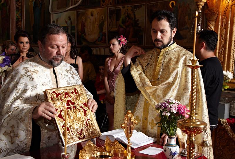 preotul se pregateste sa le citeasca mirilor din evanghelie