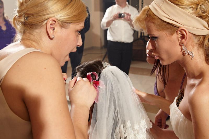 mireasa se consulta cu o prietena pentru prinderea voalului domnisoarei