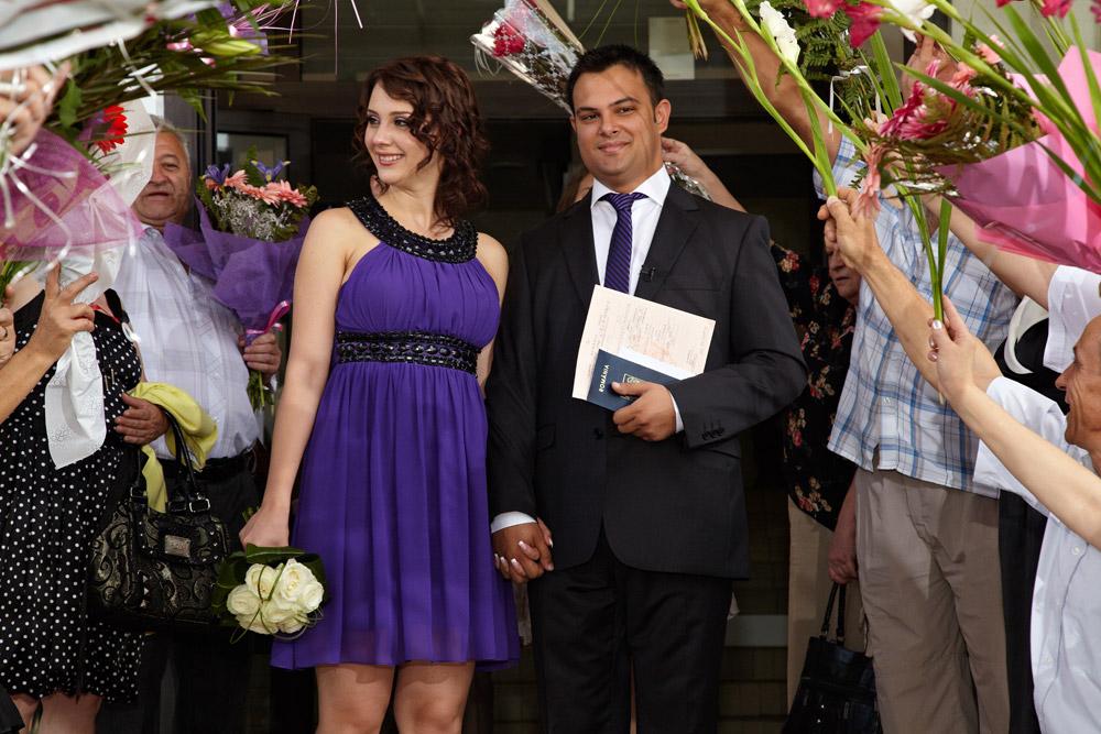 sotii sub arcada de flori la iesire din Casa de casatorii - fotografie nunta
