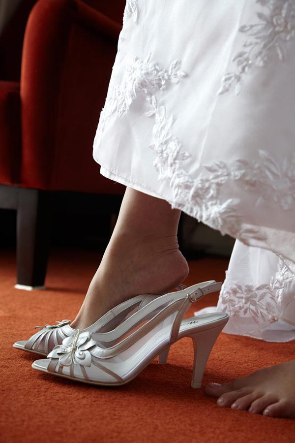 detaliu cu piciorul miresei incaltand pantoful