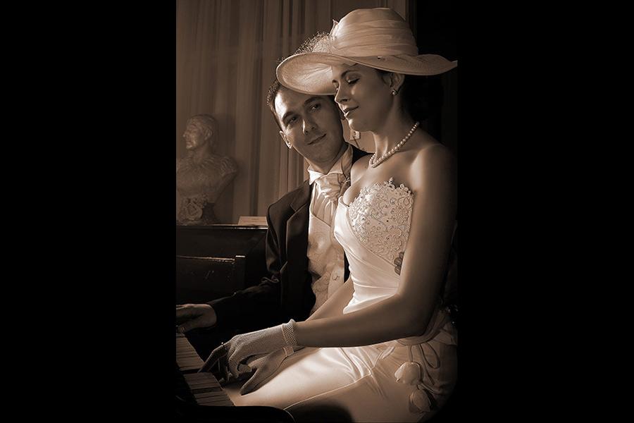fotografie cu mireasa cantand la pian asistata de mire